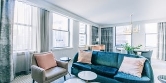 A naturally lit and open concept living room and dining area found in a suite at The Gwen