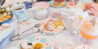 Cake bites, snacks, mixed drinks and tea cups laid on a table.
