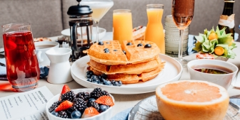 A weekend brunch served at The Gwen with a stack of blueberry waffles, fresh fruit and mimosas.