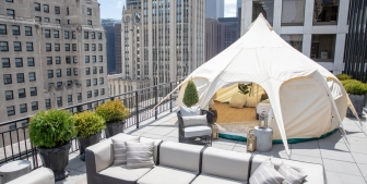 A tent setup for glamping on a balcony with a Chicago buildings in the background