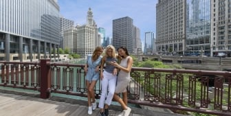 A group of ladies taking a picture on a foot bridge above the Chicago river.