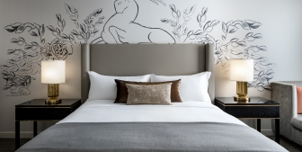 Straight on view of a bed and side tables with artwork on the wall