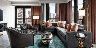 A sectional couch and two leather chairs in a hotel room.