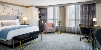 Large Chicago hotel bedroom with sitting area and desk