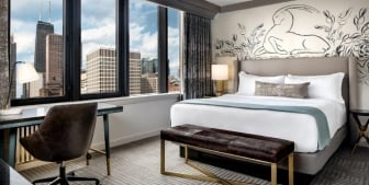 Bedroom with a large window showing off the Chicago cityscape