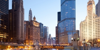 A view of the Chicago River and downtown buildings at dusk.