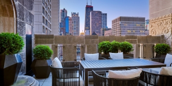 A balcony with a large outdoor table and views of downtown Chicago.