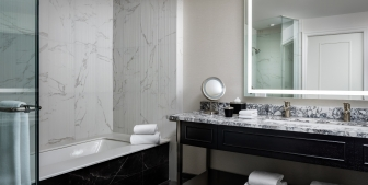 A bathroom with a full bath, large mirror and a marble countertop.