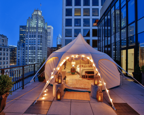 Tent with a bedroom set up on a downtown Chicago balcony with a cityscape in the background at nighttime