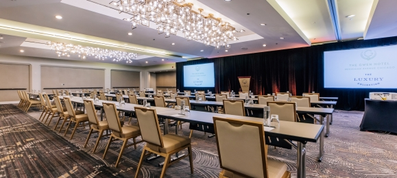 A large conference room with rows of tables, chairs and a large projector screen.