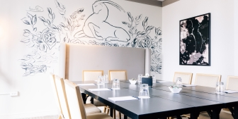 A meeting room with intricate wall art and a large table.