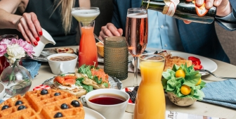 A table filled with brunch foods such as waffles, strawberries, orange juice and sparkling wine.