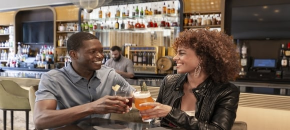 A couple smiling and enjoying drinks at Kostali in downtown Chicago.
