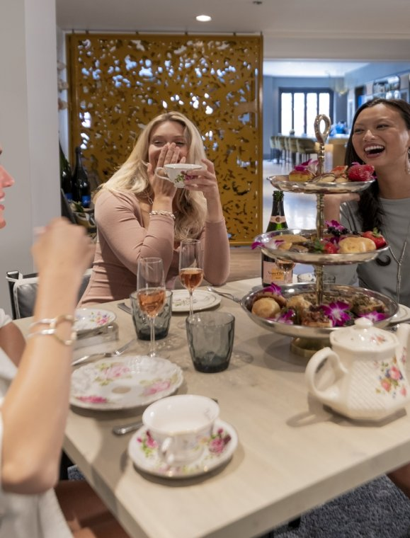 A group of ladies smiling and drinking tea.