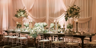 A beautifully designed head table at a wedding equipped with large candles, green bouquets and stylish décor.