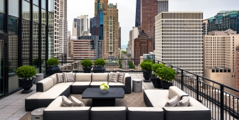 Comfortable outdoor seating and couches on a rooftop patio in downtown Chicago in The Gwen.