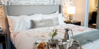 A tray of croissants and coffee laid on a hotel bed with pink rose petals spread over the duvet.