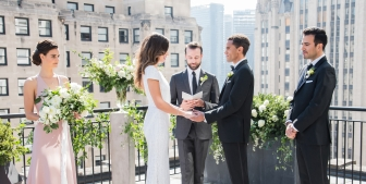 A bride and groom say their vows during their outdoor wedding on the sunny rooftop patio at The Gwen.