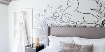 A hotel room with a large king bed with white linens and wall art.