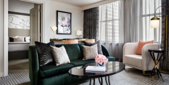 A green couch and small coffee table found in The Gwen's King Superior Suite